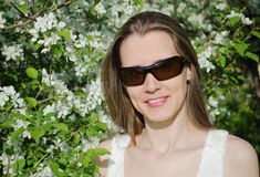 Portrait  woman with apple tree flowers. Portrait of beautiful  woman  in sun glasses with apple tree flowers in the  park Stock Photos