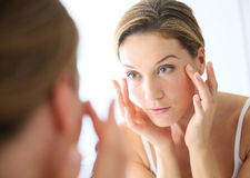 Portrait of a woman applying a cream Royalty Free Stock Photo