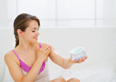 Portrait of woman applying creme on arm Stock Photography