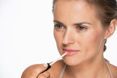 Portrait of woman applying lip gloss Royalty Free Stock Images