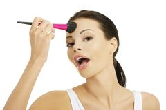 Portrait of a woman applying make up stock photos