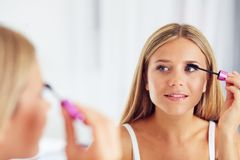 Portrait of woman applying makeup and looking in the mirror royalty free stock photo