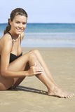 Portrait Of Woman Applying Sunscreen On Legs At Beach Stock Images