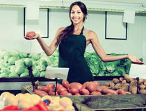 Portrait of  woman in apron selling organic potatoes in shop Royalty Free Stock Photo