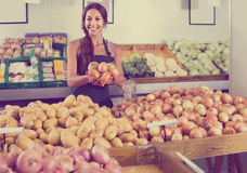 Portrait of woman in apron selling unpeeled onions Stock Photography