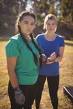 Portrait of woman assisting her friend in wearing boxing band Royalty Free Stock Photography