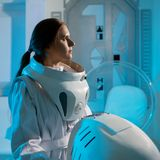 Portrait of a woman astronaut in a space suit, dreamy look up. Futuristic astronaut on Board the spacecraft. Portrait of a woman astronaut in a space suit Stock Photos