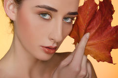Portrait of woman with autumn leaves on yellow background Stock Photo