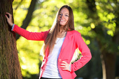 Portrait of woman in autumnal park. Portrait of young woman in pink jacket relaxing in park or forest. Autumnal scenery. Fall season Stock Images