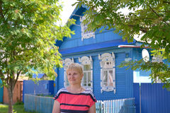 Portrait of the woman of average years against the blue wooden house Stock Image