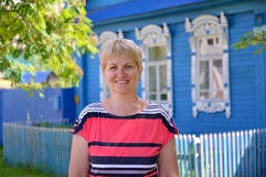 Portrait of the woman of average years against the blue wooden house Stock Photography