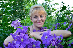 Portrait of the woman of average years among flowers Clematis Royalty Free Stock Photography