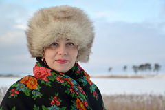 Portrait of the woman of average years in a fur cap and a colorul shawl against the winter lakef Royalty Free Stock Image