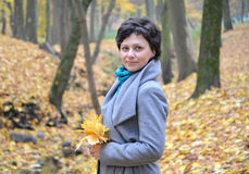 Portrait of the woman of average years with yellow maple leaves in hands. Autumn wood Stock Photography
