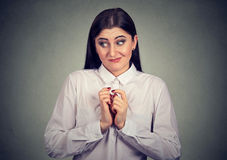 Portrait of a woman in awkward situation, playing nervously with hands. royalty free stock photo