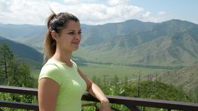 Portrait of a woman on the background of beautiful mountains. The girl stands on a panoramic platform with fluttering stock video footage