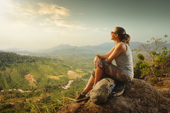 Portrait of woman with backpacker sitting on top of the mountain Royalty Free Stock Image