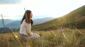Portrait of woman with backpacker sitting on top of the mountain and enjoying sunset and valley view.rMountains stock video