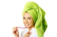 Portrait of a woman in bathrobe brushing teeth Stock Image