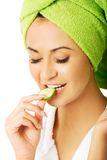 Portrait of woman in bathrobe eating cucumber Royalty Free Stock Image