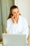 Portrait of woman in bathrobe speaking mobile. And using laptop Stock Photography
