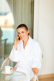 Portrait of woman in bathrobe speaking mobile. Portrait of beautiful smiling woman in bathrobe speaking mobile phone on terrace Royalty Free Stock Photography