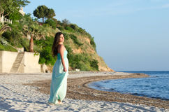 Portrait of woman at the beach wearing long coral dress Royalty Free Stock Photos
