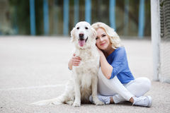 Portrait of a woman with beautiful dog playing outdoors. Stock Image