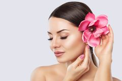 Portrait of a woman with beautiful make-up holds a Magnolia flower in his hands. stock photo