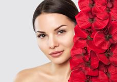 Portrait of a woman with beautiful make-up holds a red orchid in his hands. stock photo