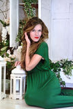 Portrait of Woman in beauty fashion green long evening dress sitting Royalty Free Stock Image