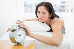 Portrait of a woman in bed extending hand to alarm clock Stock Images