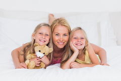 Portrait of woman in bed with her children Royalty Free Stock Images