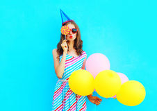 Portrait woman in a birthday cap holds an air colorful balloons is blowing lips is closes her eye with lollipop on stick. Portrait woman in a birthday cap holds Stock Photography