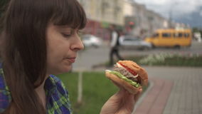 Portrait of a woman biting a burger in the street next to a busy road stock video footage