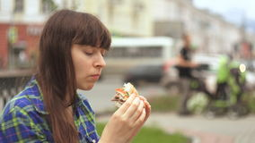 Portrait of a woman biting a burger in the street next to a busy road stock footage