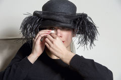 Portrait of a woman with black dress and hat looking sad Stock Images