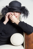 Portrait of a woman with black dress and hat looking sad. Portrait of sad woman in black with black hat stock photos