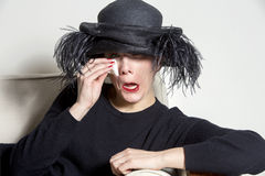 Portrait of a woman with black dress and hat looking sad. Portrait of crying woman in black with black hat royalty free stock image