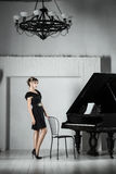 Portrait of woman in black dress sitting at the piano. Royalty Free Stock Photos