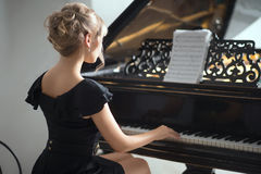 Portrait of woman in black dress sitting at the piano. Stock Photography