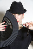 Portrait of woman with black hat and fan. Portrait of red-haired woman with black hat holding a fan and glasses stock images