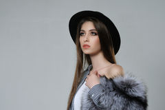 Portrait of a woman in a black hat and fur, which she holds in h. Er hand. The model is dressed in a striped shirt, her shoulder is bare Stock Images