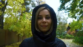 Portrait woman in black jacket with a hood walking on path in autumn day. Portrait young woman in black jacket with a hood walking on path in autumn day. Close stock video