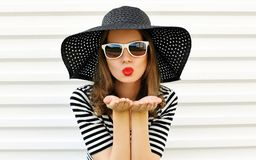 Portrait woman blowing red lips sending sweet air kiss in black summer straw hat on white wall stock photos
