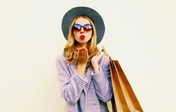 Portrait woman blowing red lips sends air kiss with shopping bags in pink coat, round hat on wall. Background stock image