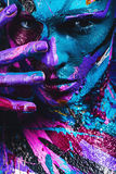 Portrait of woman in blue and pink paint with fingers on face Stock Photo