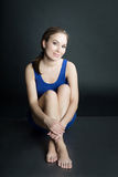 Portrait of woman in blue short dress sitting on the floor on dark background Stock Photo