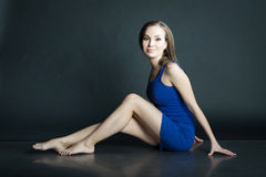 Portrait of woman in blue short dress sitting on the floor on dark background Royalty Free Stock Photography