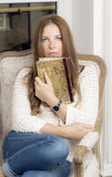 Portrait of a woman with a book. Woman sitting on chair in his hand holds a book royalty free stock photo
